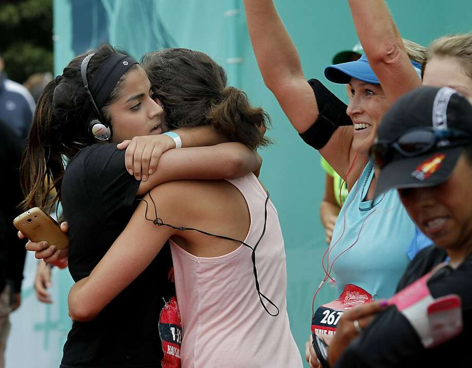 Just after the finish line, some half marathon runners stopped for a hug Sunday October 20, 2013 in San Francisco, Calif. Thousands of women and a few men took part in the annual Nike Women's Marathon which began at Union Square and finished along the Great Highway. Photo: Brant Ward, The Chronicle