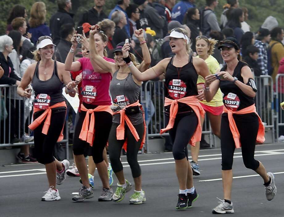 A group of runners got their smart phones ready for crossing the finish line Sunday October 20, 2013 in San Francisco, Calif. Thousands of women and a few men took part in the annual Nike Women's Marathon which began at Union Square and finished along the Great Highway. Photo: Brant Ward, The Chronicle