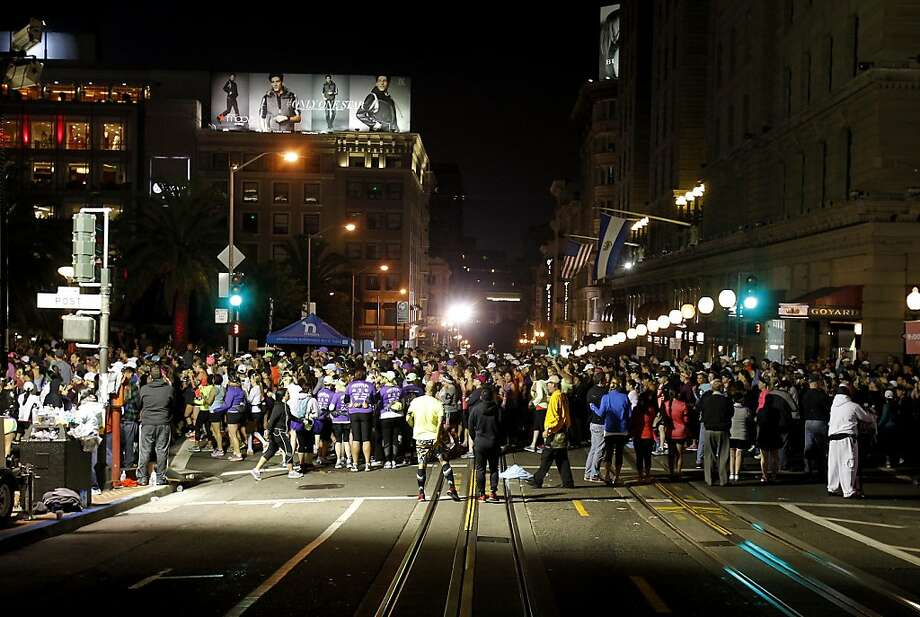 Runners crossed the cable car tracks on Powell Street Sunday October 20, 2013 in San Francisco, Calif. Thousands of women and a few men took part in the annual Nike Women's Marathon which began at Union Square and finished along the Great Highway. Photo: Brant Ward, The Chronicle