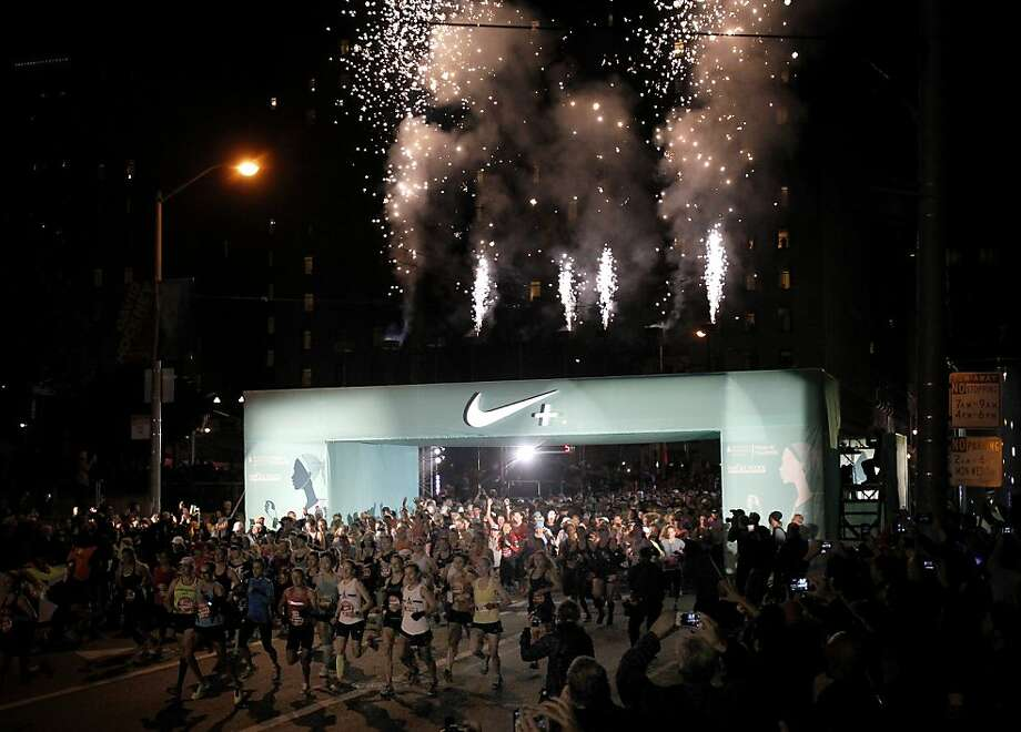 Pyrotechnics went off as the first runners left the starting line Sunday October 20, 2013 in San Francisco, Calif. Thousands of women and a few men took part in the annual Nike Women's Marathon which began at Union Square and finished along the Great Highway. Photo: Brant Ward, The Chronicle