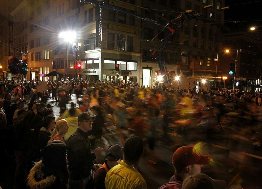 Runners from the first wave moved down Post Street on their way to the Embarcadero Sunday October 20, 2013 in San Francisco, Calif. Thousands of women and a few men took part in the annual Nike Women's Marathon which began at Union Square and finished along the Great Highway. Photo: Brant Ward, The Chronicle