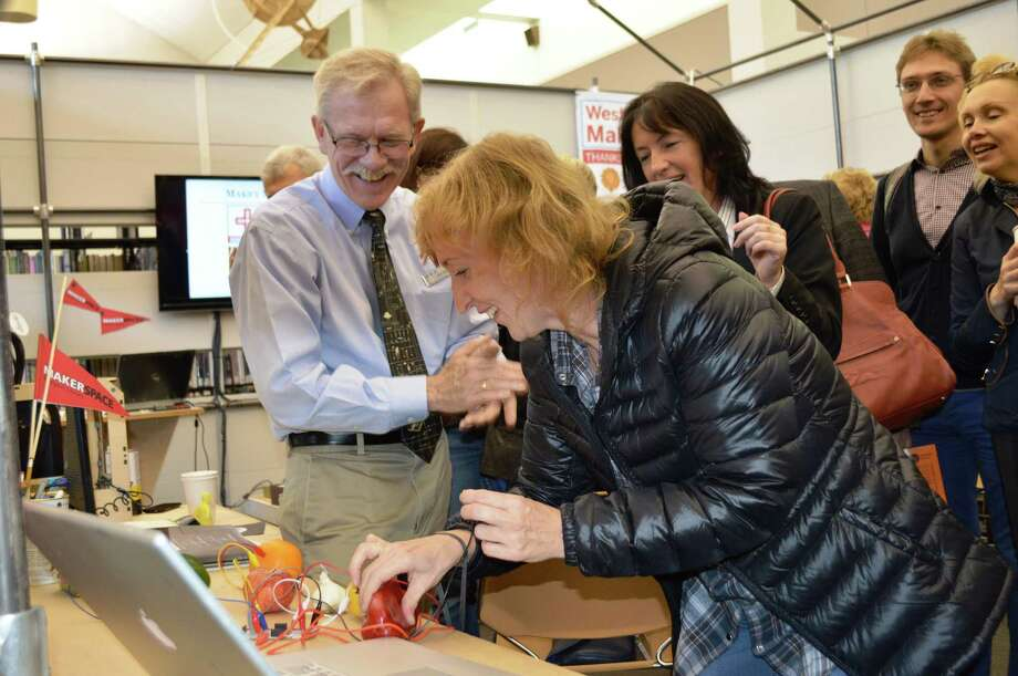 Bill Derry, left, assistant direcotor of the Westport Library, delighted visiting Russian librarians Sunday morning by showing them how to play a song with vegetables hooked up to a computer. Nearly 20 Russian librarians are on a tour of U.S. libraries viewing new innovations, and they stopped in Westport to see its MakerSpace, an area set aside for development of innovations. Photo: Contributed Photo / Westport News