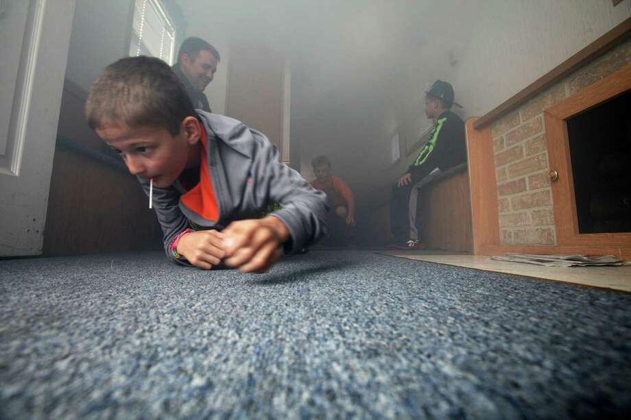 Jake Sanderson, 9, of Trumbull, crawls through a fire prevention trailer, from Westport, at the Long Hill Volunteer Fire Dept.'s annual open house in Trumbull, Conn. on Sunday, Oct. 20, 2013. Photo: Unknown, B.K. Angeletti / Connecticut Post freelance B.K. Angeletti
