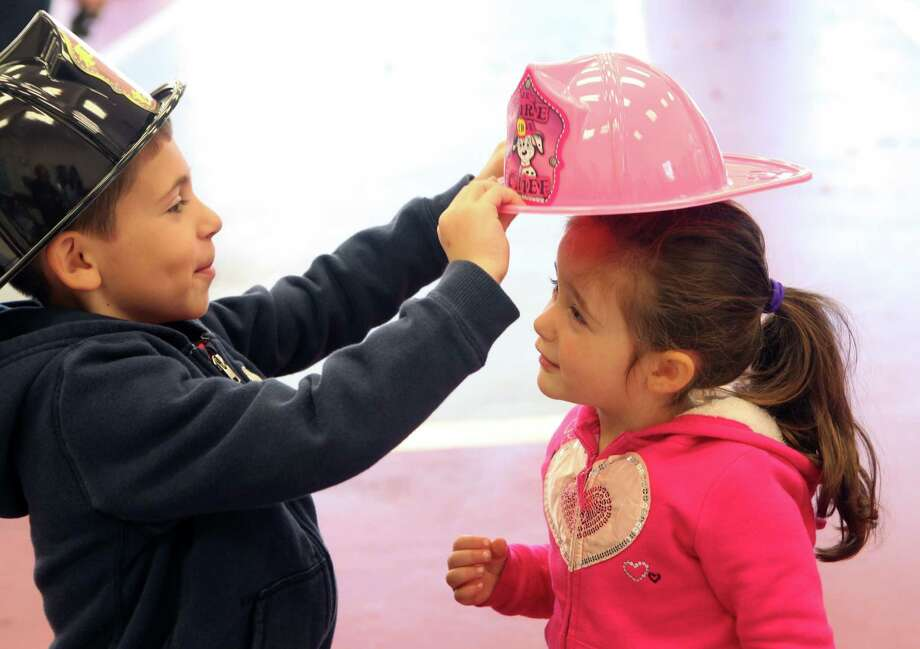 Anthony Elliano, 6, of Trumbull, puts a helmut on his sister, Sofia, 3, during the Long Hill Volunteer Fire Dept.'s annual open house in Trumbull, Conn. on Sunday, Oct. 20, 2013. Photo: Unknown, B.K. Angeletti / Connecticut Post freelance B.K. Angeletti