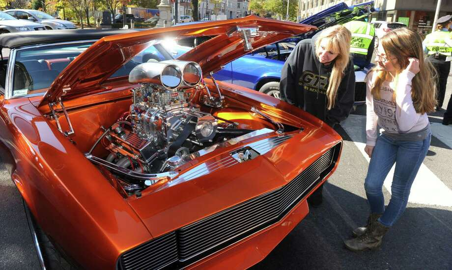 "Denise Rafferty and her daughter, Kaleigh, 12, right, look over a 1968 Chevy Camero during a "" Classic Car & Bike Show on Main Street""  in Danbury, Conn. Sunday, Oct. 20, 2013. In the tradition of previous ""Karing for Kelly"" events, the charity event is hosted by Lew Lombardo's Ultimate Restorations LLC, and George Korres's Nico's Pizza and Pasta, to benefit Danbury firefighter Joe LaDuca, who is suffering malignant brain tumors. Photo: Michael Duffy / The News-Times"