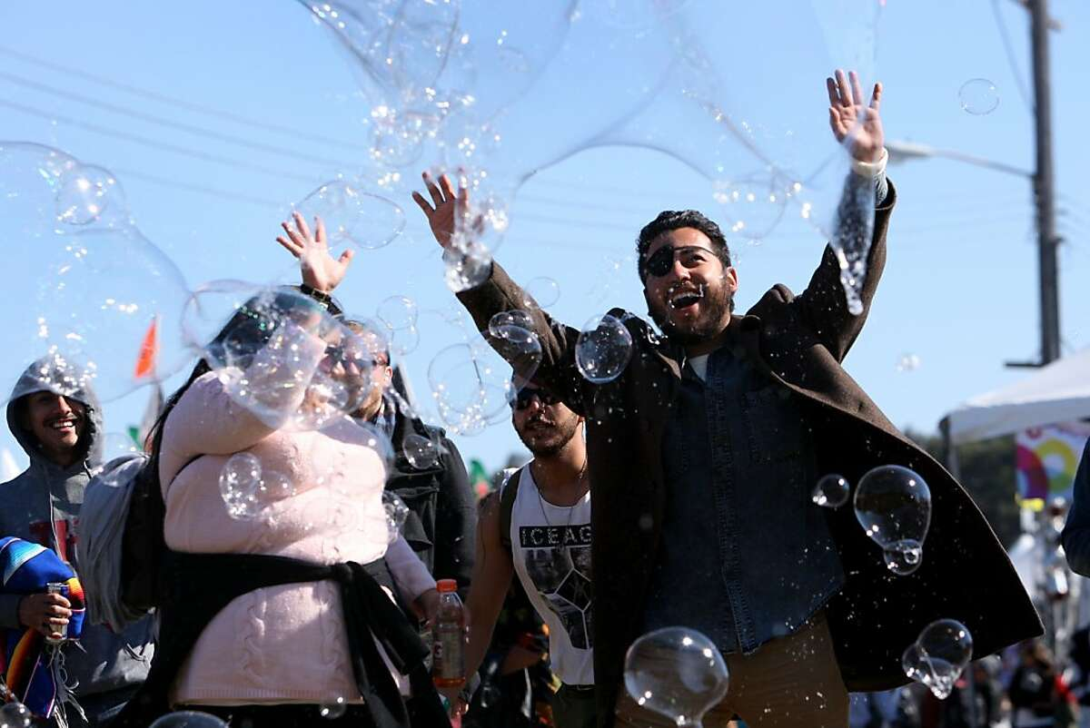 Cesar Gonzalez cheers as he reaches to pop bubbles at the Treasure Island Music Festival in San Francisco, Calif. on Sunday, Oct. 20, 2013.