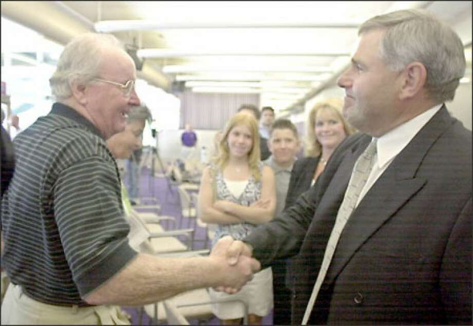 Former UW coach Keith Gilbertson basks in the presence of his mentor, UW legend Don James. Photo: The Associated Press