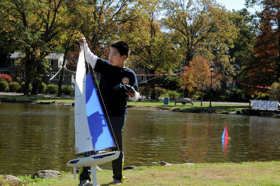 Alex Liu, 11, of Greenwich, fixes his sail at Old Greenwich- Riverside Civic Center's 51st annual Model Saiboat Regatta in Binney Park, Conn., Sunday, Oct. 20, 2013. Photo: Helen Neafsey / Greenwich Time