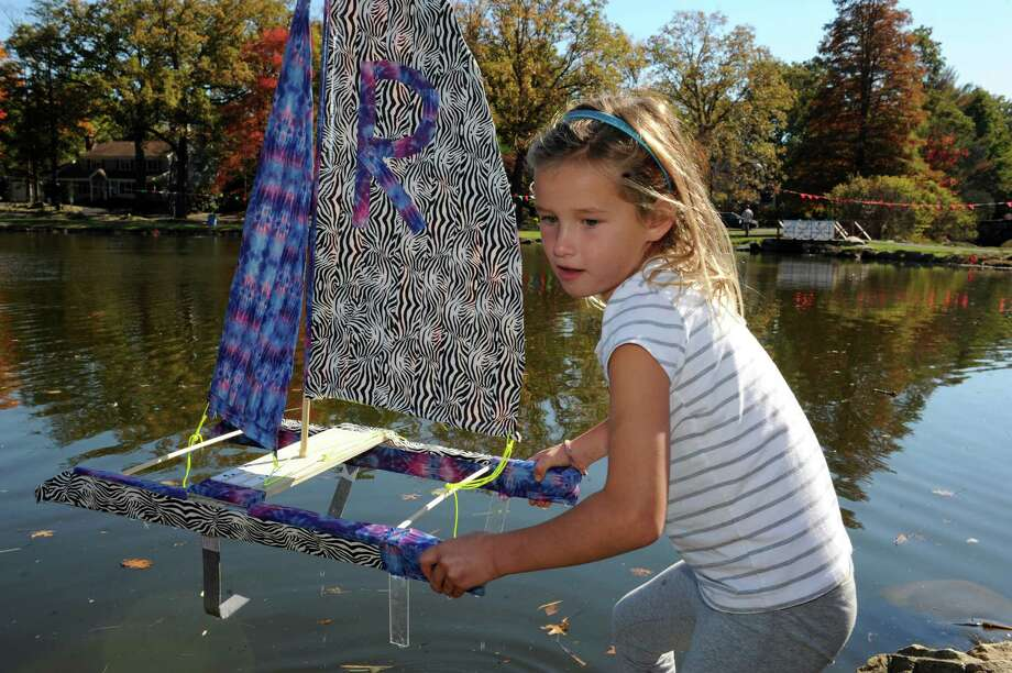 Reese-Bennett Clark, 6, of Greenwich, brings her sailboat to the pond at Old Greenwich- Riverside Civic Center's 51st annual Model Saiboat Regatta in Binney Park, Conn., Sunday, Oct. 20, 2013. Photo: Helen Neafsey / Greenwich Time