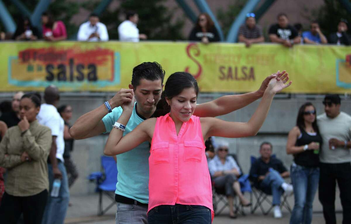 Oscar Hernandez leads Darinka Gutierrez while dancing salsa during El Festival De La Salsa at Jones Plaza on Sunday, Oct. 20, 2013, in Houston.
