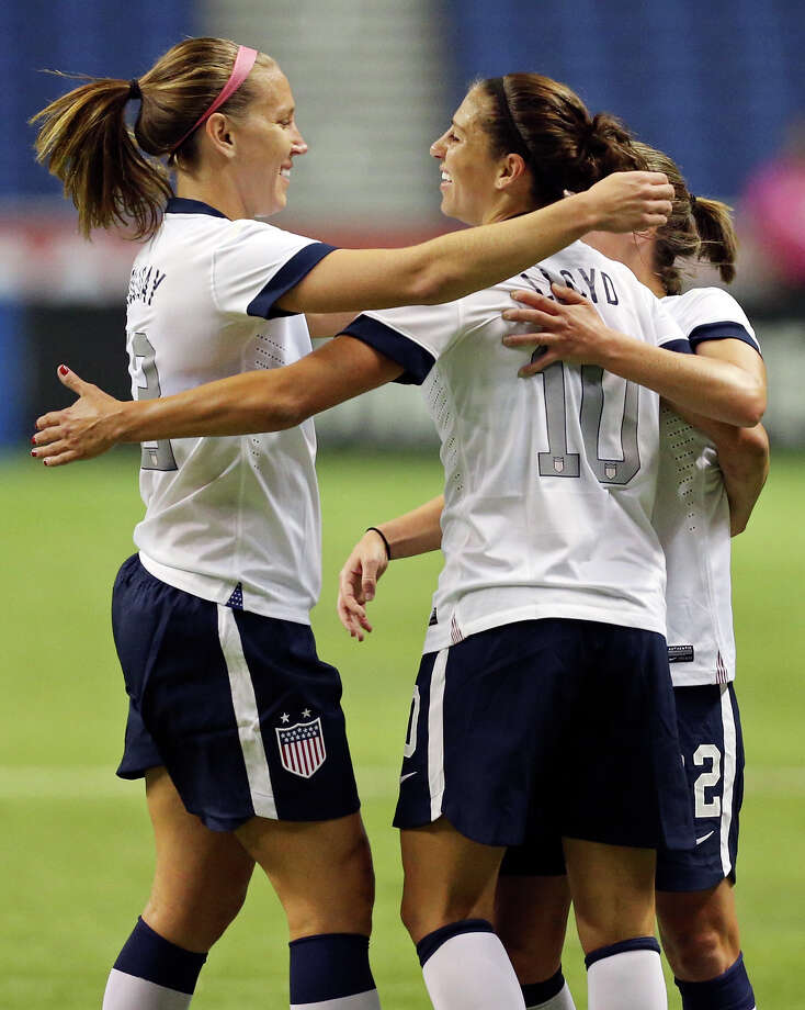 United States of America's Carli Lloyd (center) celebrates with teammates Lauren Holiday (left) and Meghan Klingenberg after scoring a goal against Australia during first half action of an international friendly soccer match Sunday Oct. 20, 2013 at the Alamodome. Photo: Edward A. Ornelas, San Antonio Express-News / © 2013 San Antonio Express-News