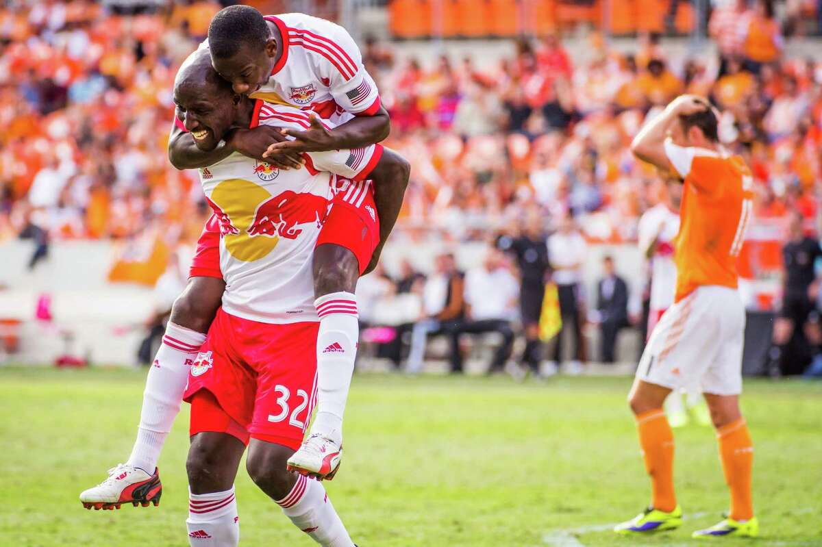 New York Red Bulls defender Ibrahim Sekagya (32) celebrates with forward Bradley Wright-Phillips after scoring during the 75th minute as Houston Dynamo midfielder Brad Davis (11) walks away during an MLS soccer match on Sunday, Oct. 20, 2013, at BBVA Compass Stadium.