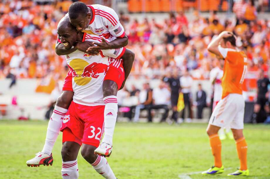 New York Red Bulls defender Ibrahim Sekagya (32) celebrates with forward Bradley Wright-Phillips after scoring during the 75th minute as Houston Dynamo midfielder Brad Davis (11) walks away during an MLS soccer match on Sunday, Oct. 20, 2013, at BBVA Compass Stadium. Photo: Smiley N. Pool, Houston Chronicle / © 2013  Houston Chronicle