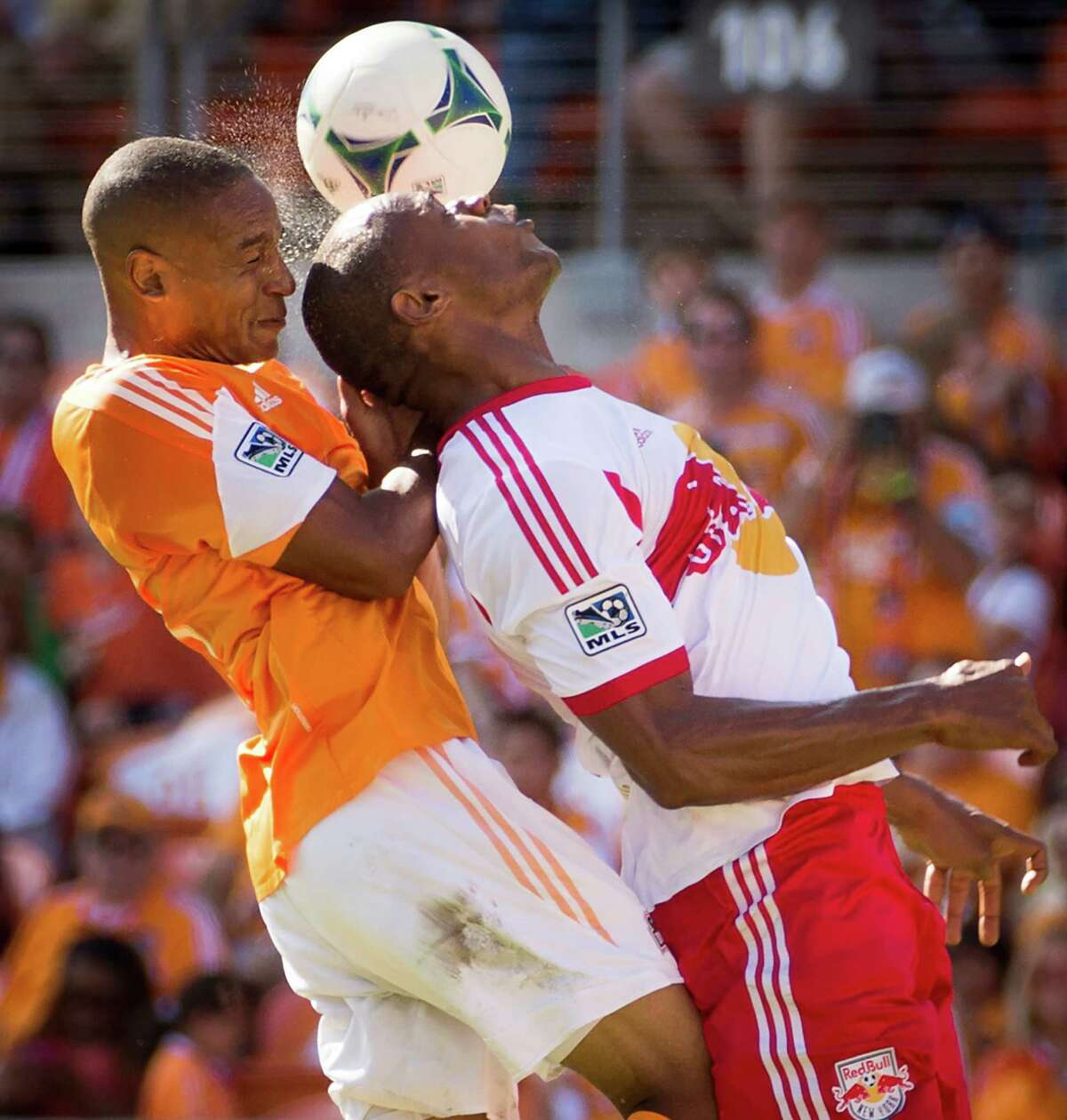 Dynamo midfielder Ricardo Clark, left, fights for a header against Red Bulls defender Jamison Olave.