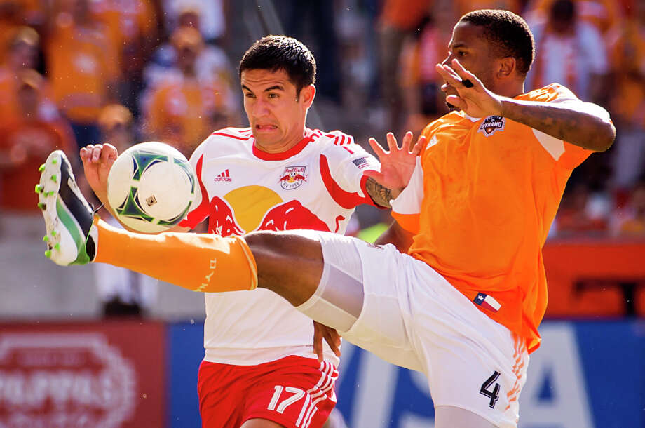 Dynamo defender Jermaine Taylor (4) fights for the ball against Red Bulls midfielder Tim Cahill (17). Photo: Smiley N. Pool, Houston Chronicle / © 2013  Houston Chronicle