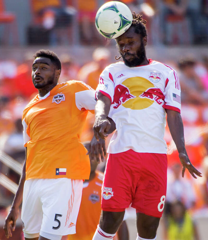 Red Bulls forward Peguy Luyindula (88) wins a header from Dynamo defender Warren Creavalle (5). Photo: Smiley N. Pool, Houston Chronicle / © 2013  Houston Chronicle