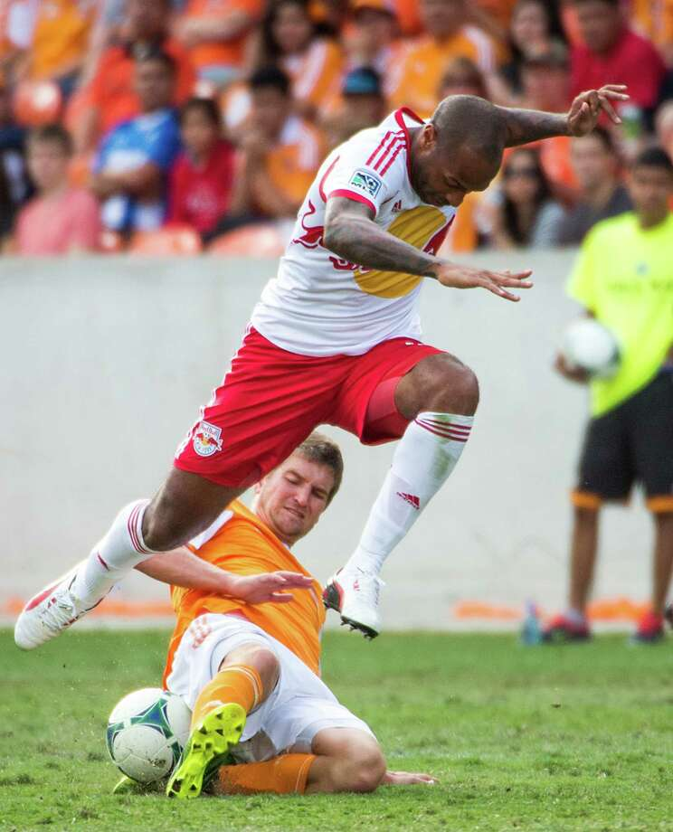 Red Bulls forward Thierry Henry leaps over Dynamo defender Bobby Boswell. Photo: Smiley N. Pool, Houston Chronicle / © 2013  Houston Chronicle