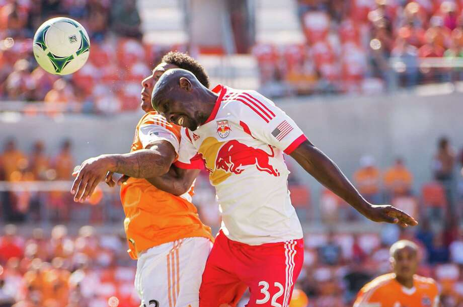 Red Bulls defender Ibrahim Sekagya (32) fights for a header against Dynamo midfielder Giles Barnes. Photo: Smiley N. Pool, Houston Chronicle / © 2013  Houston Chronicle