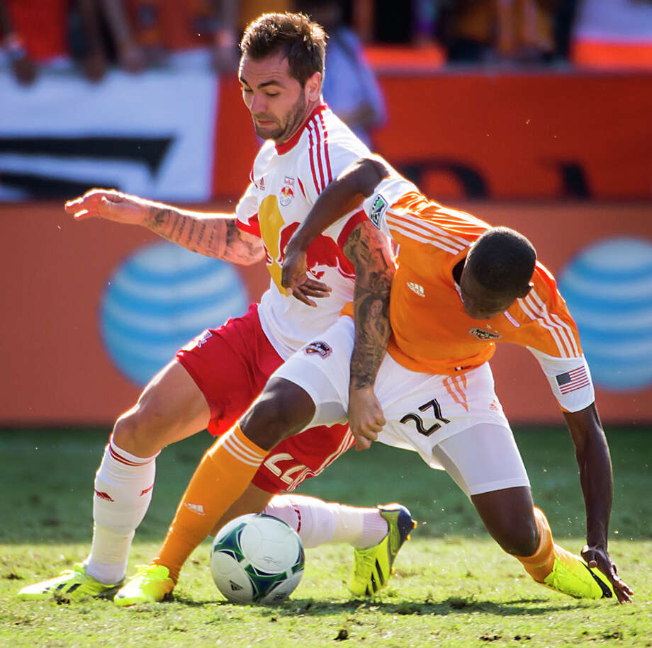 Dynamo midfielder Boniek Garcia (27) tangles with Red Bulls midfielder Jonny Steele. Photo: Smiley N. Pool, Houston Chronicle / © 2013  Houston Chronicle