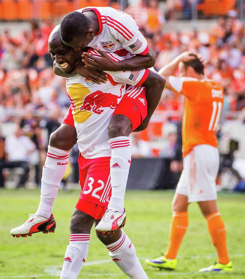 Red Bulls defender Ibrahim Sekagya (32) celebrates with forward Bradley Wright-Phillips after scoring during the 75th minute. Photo: Smiley N. Pool, Houston Chronicle / © 2013  Houston Chronicle