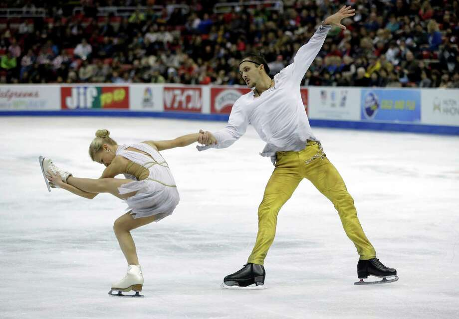 Tatiana Volosozhar, left, and Maxim Trankov, of Russia, perform during the pairs free skating routine at the Skate America figure skating competition in Detroit, Sunday, Oct. 20, 2013. (AP Photo/Carlos Osorio) ORG XMIT: MICO301 Photo: Carlos Osorio / AP