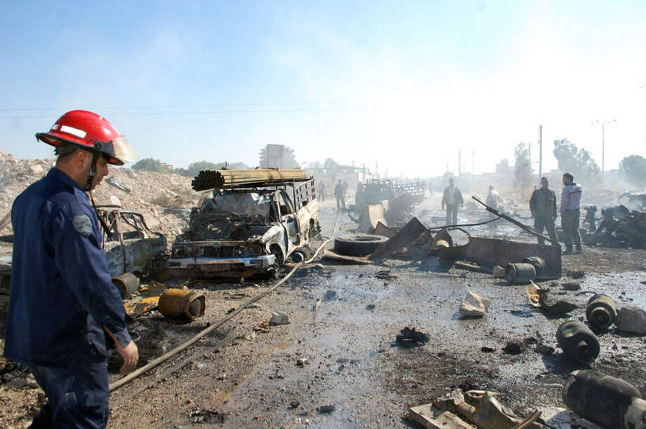 A photo released by the official Syrian Arab News Agency shows the scene of a car bombing in the central city of Hama that killed more than 30 people, ignited dozens of cars and sent up a column on smoke visible for miles. Photo: Getty Images