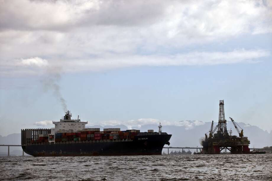 An oil platform sits under repair, back right, as a container ship passes by in Guanabara Bay, offshore from Niteroi, Brazil, on Friday, Sept. 27, 2013. Photo: Dado Galdieri, Bloomberg