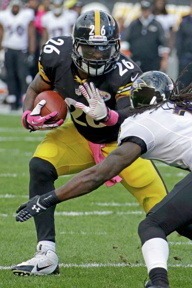 Pittsburgh Steelers running back Le'Veon Bell, left, runs the ball as Baltimore Ravens cornerback Lardarius Webb tries for the tackle in the first quarter of an NFL football game in Pittsburgh on Sunday, Oct. 20, 2013. (AP Photo/Gene J. Puskar) ORG XMIT: PAKS111 Photo: Gene J. Puskar / AP