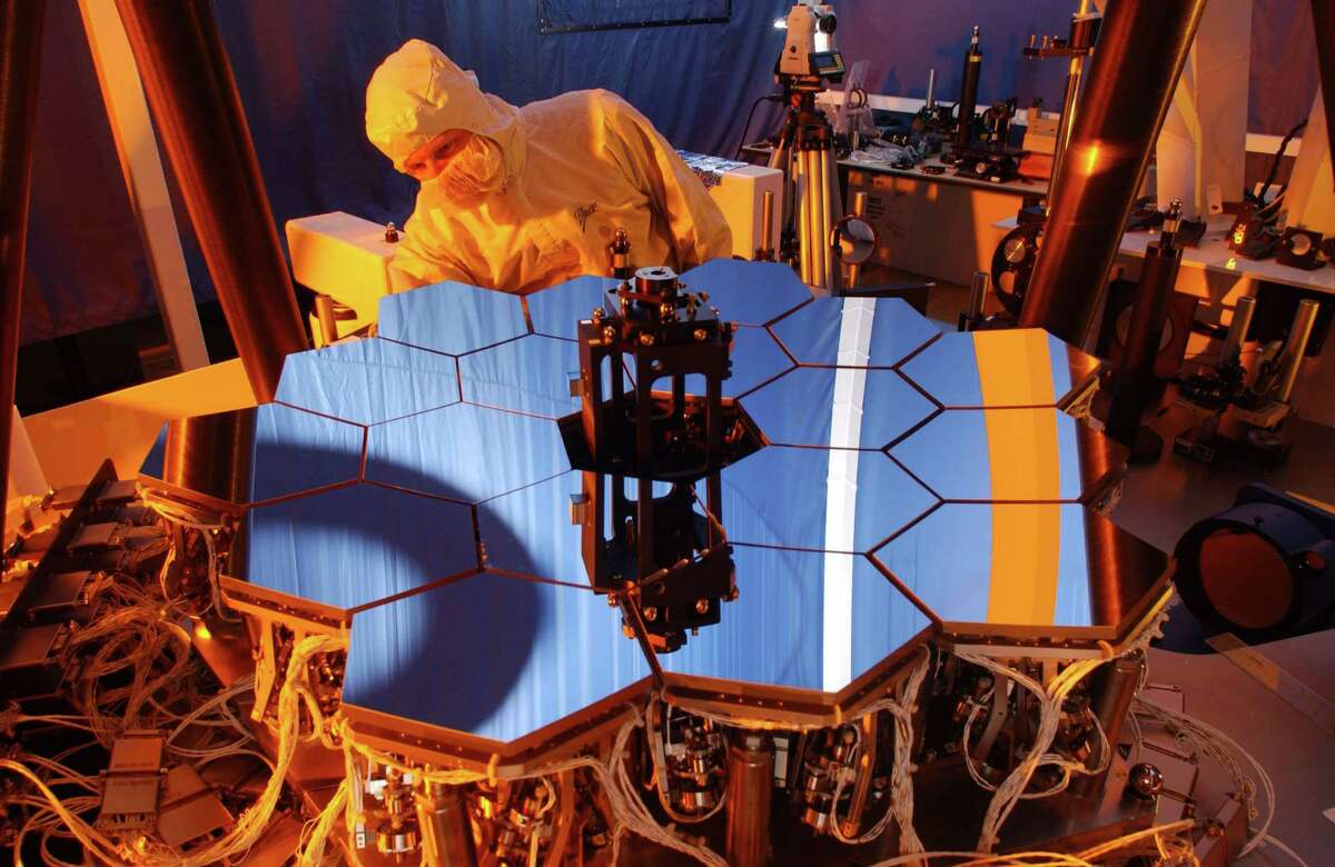 A Ball Aerospace engineer inspects the James Webb Space Telescope testbed telescope. As the principal subcontractor for Northrop Grumman Corporation, Ball Aerospace is contributing the advanced optical technology and lightweight mirror system for JWST. (PRNewsFoto/Ball Aerospace & Technologies Corp.)