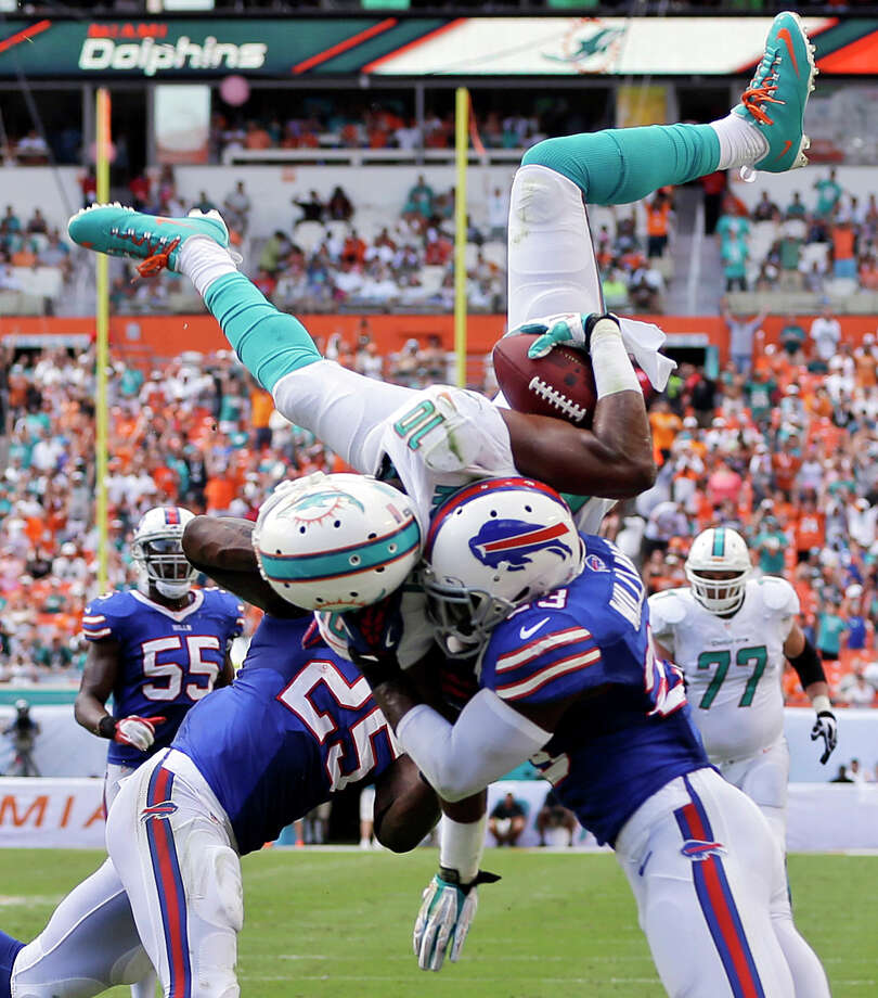 Miami Dolphins wide receiver Brandon Gibson (10) jumps over Buffalo Bills free safety Aaron Williams (23) and strong safety Da'Norris Searcy (25) for a touchdown during the first half of an NFL football game, Sunday, Oct. 20, 2013, in Miami Gardens, Fla. (AP Photo/Lynne Sladky) ORG XMIT: SLS210 Photo: Lynne Sladky / AP