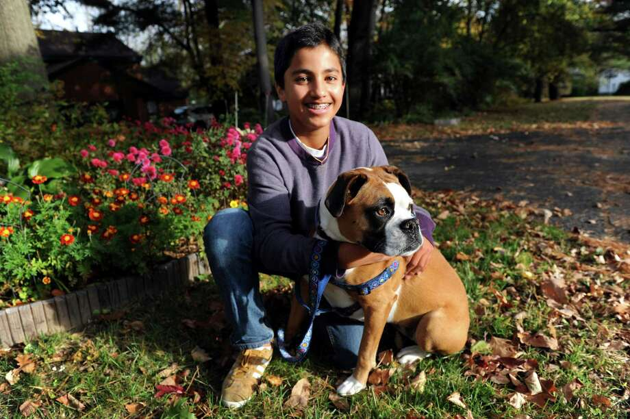 Alec Devaprasad, 14, and his boxer, Mia, on Friday, Oct. 11, 2013, in Delmar, N.Y. Alec co-owns his own pet care business, called Playful Pup Pet Care. (Cindy Schultz / Times Union) Photo: Cindy Schultz / 00024236A