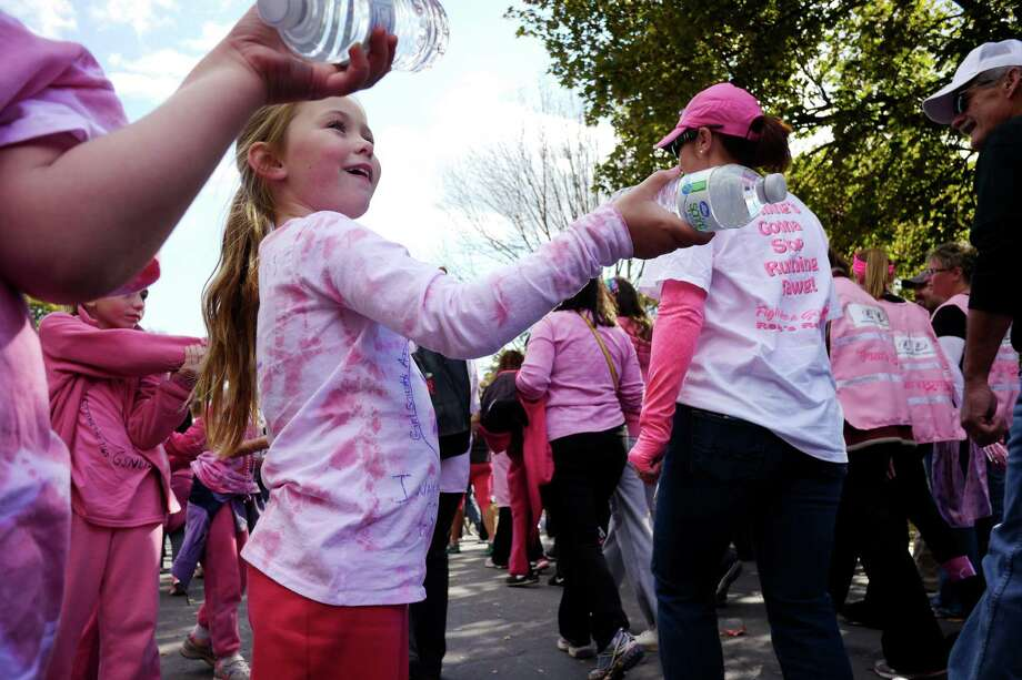 Girl Scout, Cathryn Phillips, 7, from Troy Troop 1165, along with her fellow scouts, hand out bottles of water to people during the Making Strides Against Breast Cancer Walk at Washington Park on Sunday, Oct. 20, 2013 in Albany, NY.  Organizers said that $1 million dollars was raised at the Albany event and they were expecting 15,000 people to take part in the walk.  For the Eastern Division of the American Cancer Society, which covers New York and New Jersey, 24 walks were held and a total of $20 million dollars was raised, according to organizers.   (Paul Buckowski / Times Union) Photo: Paul Buckowski / 00024068A