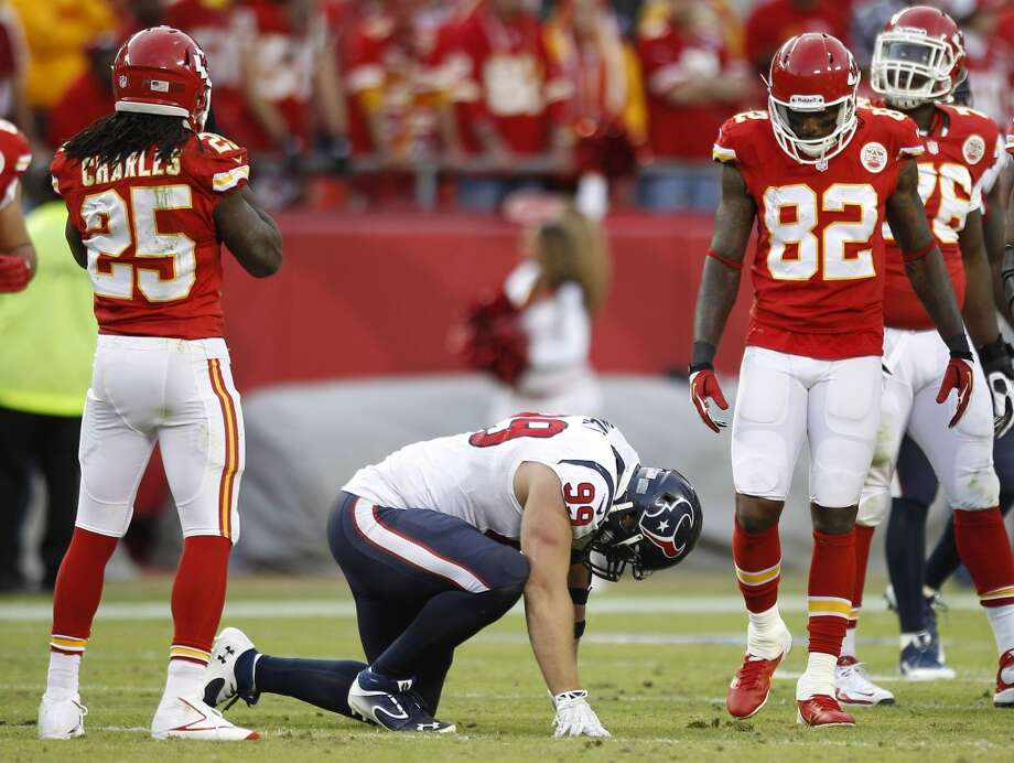Texans defensive end J.J. Watt (99) kneels on the field after being shaken up. Photo: Brett Coomer, Houston Chronicle