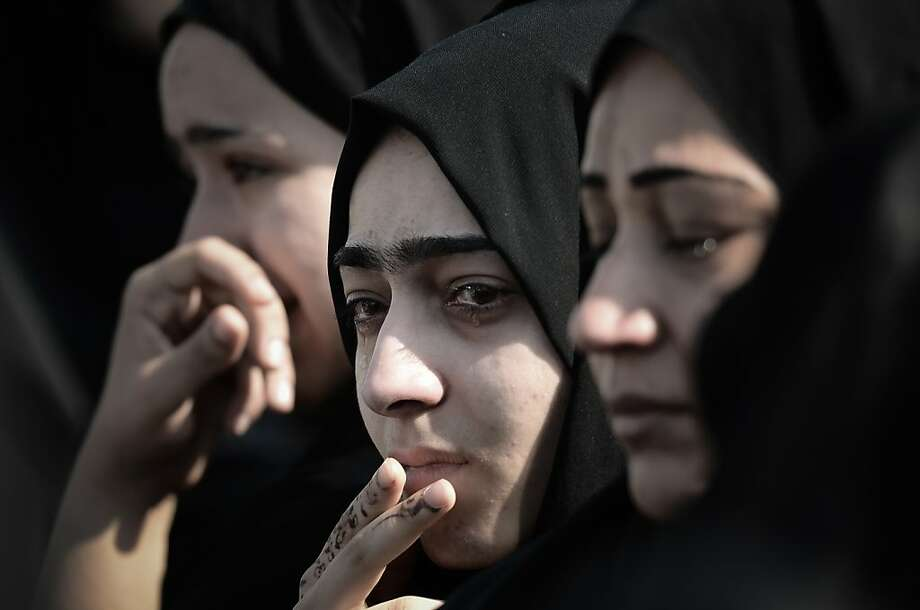 Bahraini women mourn during the funeral of Hussain Mahdi Habib in the village of Sitra, south of Manama, on October 20, 2013. Habib, 20, a political prisoner who escaped from prison on May 19, was found the day before after he was allegedly shot dead near Al Malkiyah coastal village.    TOPSHOTS/AFP PHOTO/MOHAMMED AL-SHAIKHMOHAMMED AL-SHAIKH/AFP/Getty Images Photo: Mohammed Al-shaikh, AFP/Getty Images