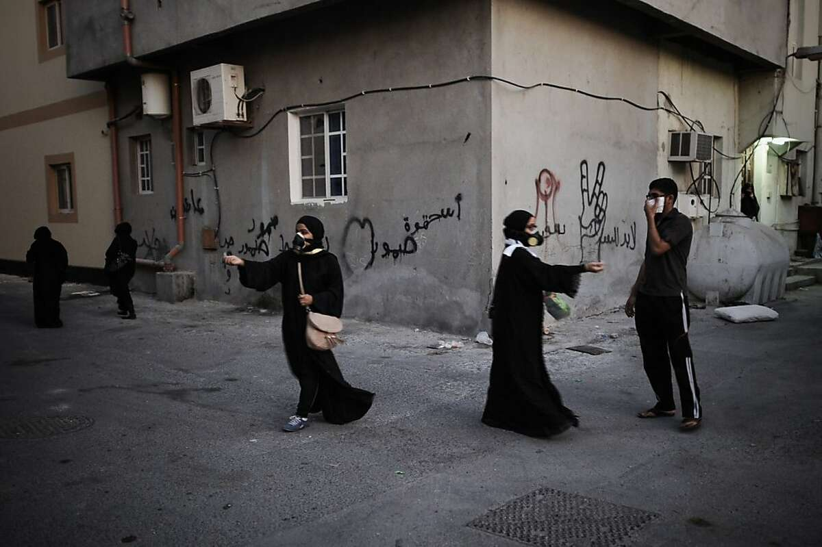 Bahraini women wear tear gas masks, as they try to treat protestors affected from the tear gas during clashes with riot police following the funeral of Hussain Mahdi Habib in the village of Sitra, south of Manama, on October 20, 2013. Habib, 20, a political prisoner who escaped from prison on May 19, was found the day before after he was allegedly shot dead near Al Malkiyah coastal village. TOPSHOTS/AFP PHOTO/MOHAMMED AL-SHAIKHMOHAMMED AL-SHAIKH/AFP/Getty Images