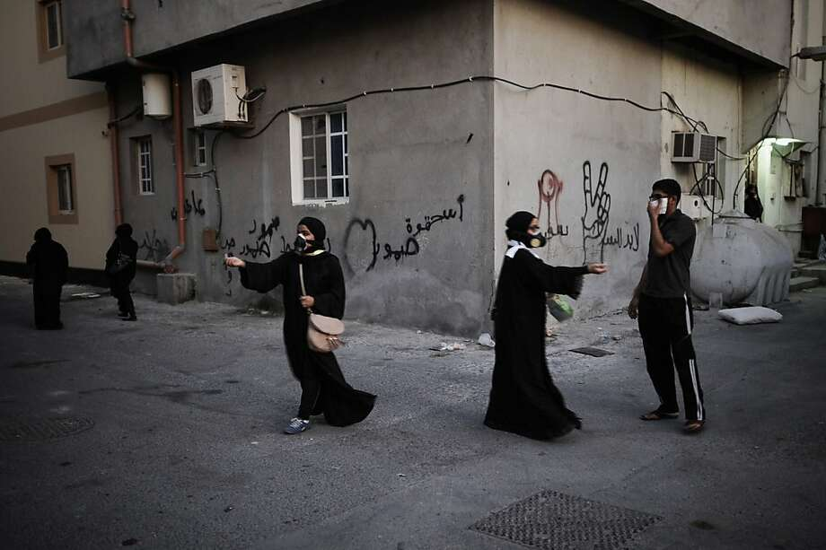 Bahraini women wear tear gas masks, as they try to treat protestors affected from the tear gas during clashes with riot police following the funeral of Hussain Mahdi Habib in the village of Sitra, south of Manama, on October 20, 2013.  Habib, 20, a political prisoner who escaped from prison on May 19, was found the day before after he was allegedly shot dead near Al Malkiyah coastal village.     TOPSHOTS/AFP PHOTO/MOHAMMED AL-SHAIKHMOHAMMED AL-SHAIKH/AFP/Getty Images Photo: Mohammed Al-shaikh, AFP/Getty Images