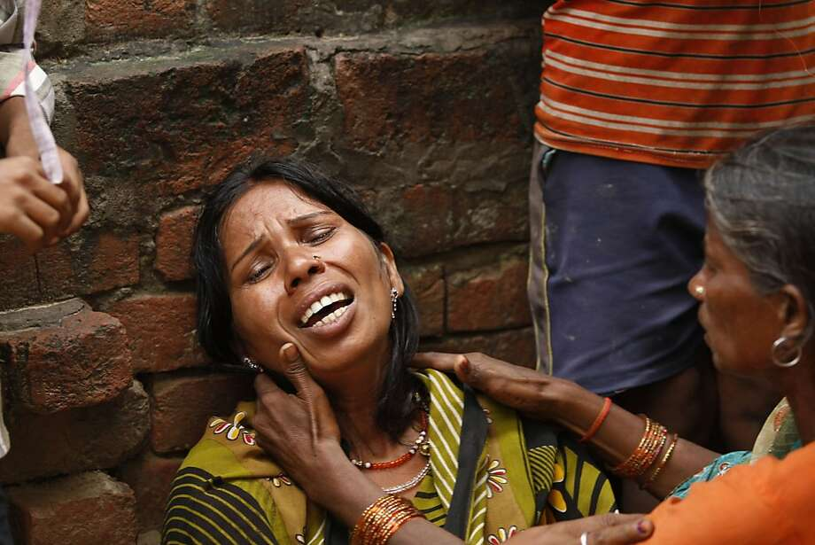 Indian woman Poonam, whose two relatives died after drinking toxic bootleg liquor, wails at Atardiha village in Azamgarh district, some 300 kilometers (185 miles) southeast of Lucknow, India, Sunday, Oct.20, 2013. Dozens of people died and some 40 people are being treated in hospitals after drinking the toxic drink in Uttar Pradesh state, police said. Deaths from drinking illegally brewed alcohol are common in India because the poor cannot afford licensed liquor. Illicit liquor is often spiked with chemicals such as pesticides to increase potency.(AP Photo/ Rajesh Kumar Singh) Photo: Rajesh Kumar Singh, Associated Press
