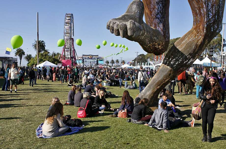 "Festival goers sit beneath the ""Bliss Dance"" sculpture at the Treasure Island Music Festival in San Francisco, Calif. on Sunday, Oct. 20, 2013. Photo: Raphael Kluzniok, The Chronicle"