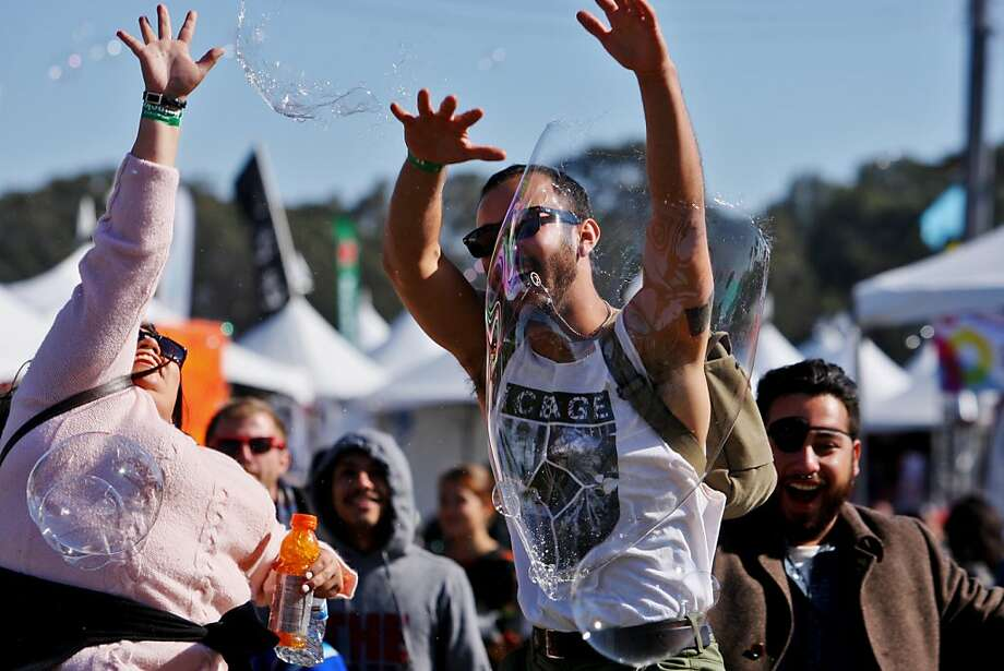 Ivana Robles and Ray Hernandez reach to pop bubbles at the Treasure Island Music Festival in San Francisco, Calif. on Sunday, Oct. 20, 2013. Photo: Raphael Kluzniok, The Chronicle