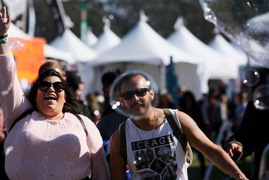 Ivana Robles and Ray Hernandez stand in the path of bubbles waiting to pop them at the Treasure Island Music Festival in San Francisco, Calif. on Sunday, Oct. 20, 2013. Photo: Raphael Kluzniok, The Chronicle