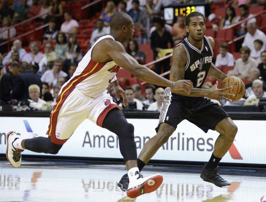 Spurs forward Kawhi Leonard, driving past Miami's Dwyane Wade, had a team-high 17 points in Saturday's preseason loss. Photo: Lynne Sladky / Associated Press