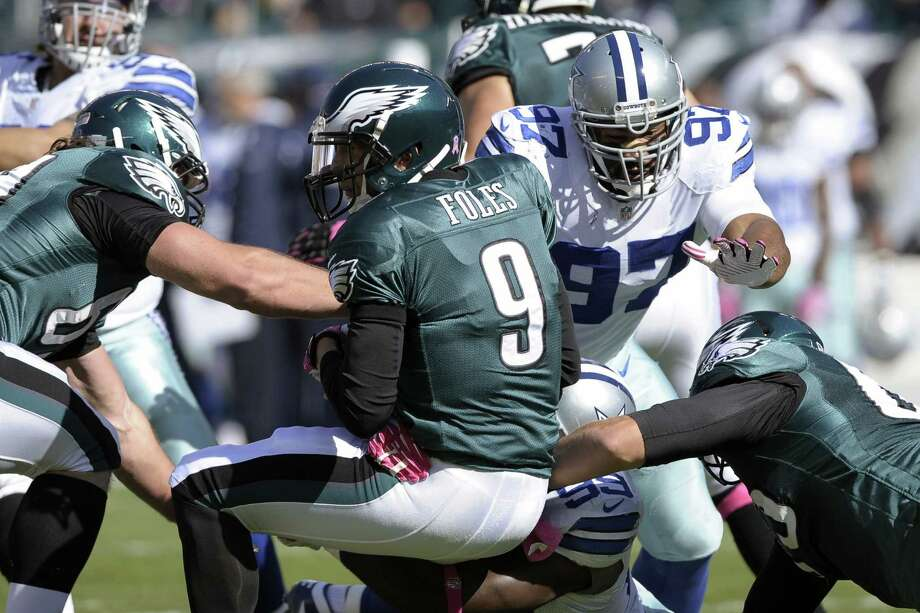 Eagles quarterback Nick Foles, an Austin Westlake graduate, is sacked by Cowboys defensive end George Selvie (bottom) as defensive tackle Jason Hatcher (97) helps out. Dallas had three sacks and knocked Foles from Sunday's game with a head injury. Photo: Michael Perez / Associated Press