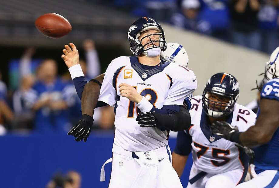 Peyton Manning loses control of the ball as he is hit. The Broncos committed three turnovers. Photo: Andy Lyons, Getty Images