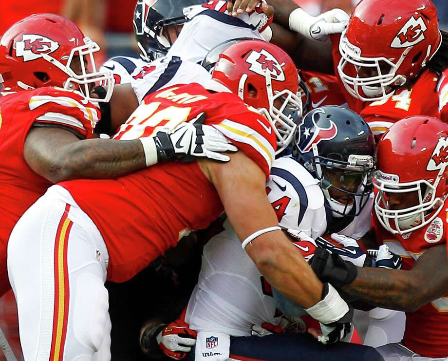 Four Chiefs descend on Texans running back Ben Tate (44) to stop him at the line of scrimmage. With backfield mate Arian Foster out with a hamstring injury early, Tate saw plenty of Chiefs red and minutes, carrying the ball 15 times for 50 yards. Photo: Brett Coomer, Staff / © 2013  Houston Chronicle