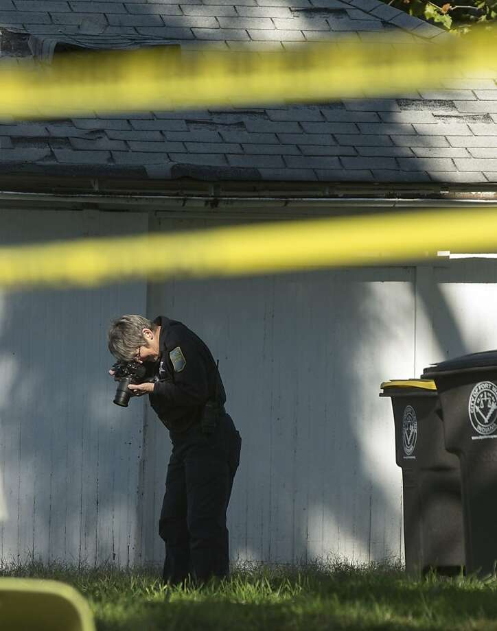 A Fort Wayne police officer takes photos in the backyard of 1230 W. Wildwood Avenue in Fort Wayne, Ind., as officers investigate a fatal shooting that happened there shortly after noon on Sunday, Oct. 20, 2013. The shooting was the third fatal shooting in the last five days in the city, which is already well above a 15-year high in homicides and is pushing toward the all-time high of 43 in 1997.  (AP Photo/The Journal Gazette, Chad Ryan) Photo: Chad Ryan, Associated Press