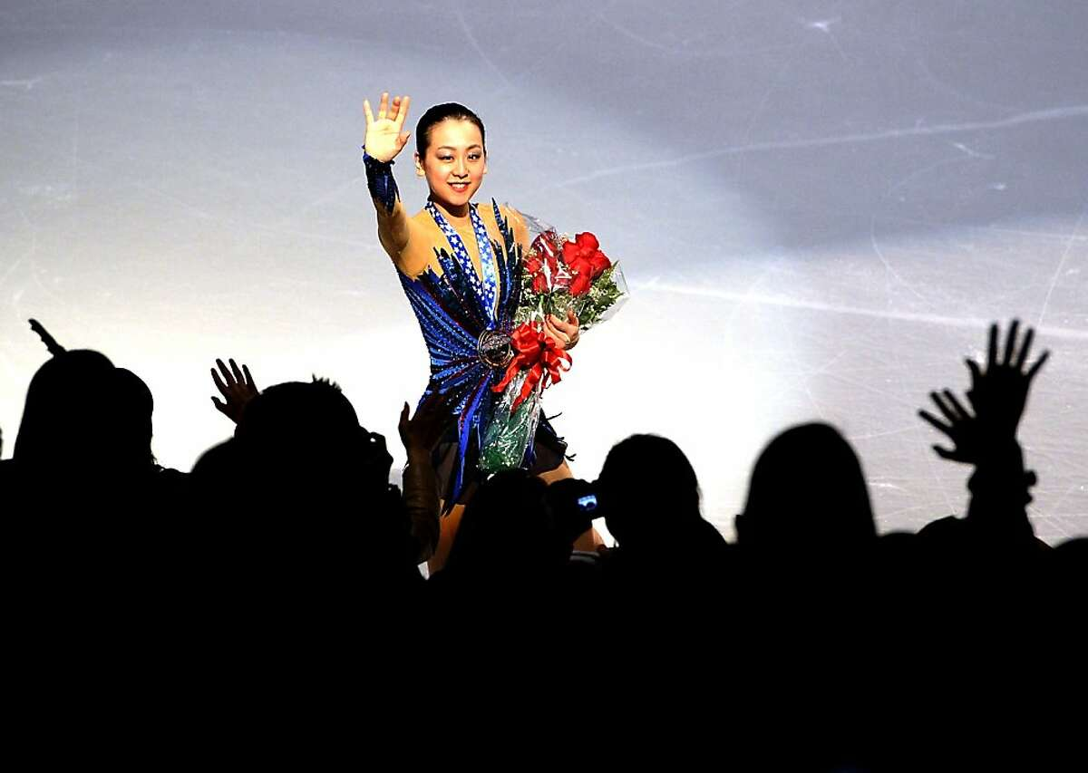 DETROIT, MI - OCTOBER 20: Mao Asada of Japan waves to fans with he gold medal after the ladies free at Skate America 2013 at the Joe Louis Arena on October 20, 2013 in Detroit, Michigan. (Photo by Harry How/Getty Images)