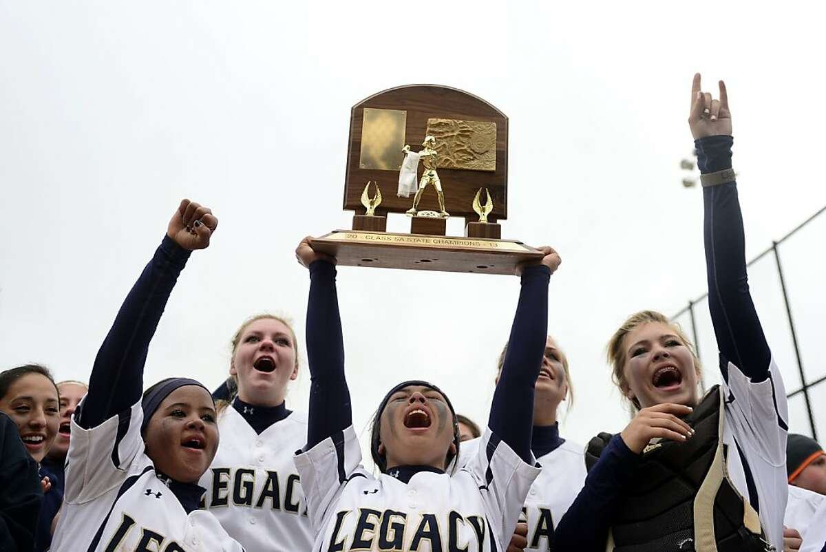 Legacy's Aspen Eubanks hoists the trophy as Legend players look on following the Lightning's 6-4 state title win Sunday Oct. 20, 2013 at the Aurora Sports Park in Aurora, Colo.. The win was Legacy's sixth title in seven years. (AP Photo/The Denver Post, AAron Ontiveroz)