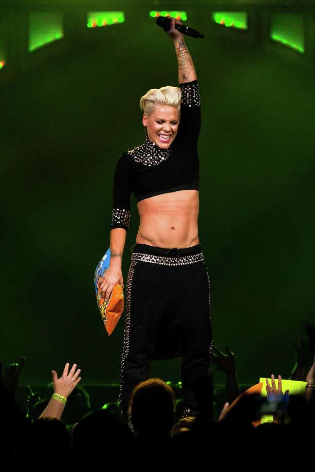 "Clutching a bag of Cheetos thrown to her by a fan, P!nk performs on the opening night of her ""The Truth About Love Tour"" Sunday, Oct. 20, 2013, at KeyArena in Seattle. The 30-stop tour kicked off in Seattle and will conclude Brooklyn. Photo: JORDAN STEAD, SEATTLEPI.COM / SEATTLEPI.COM"