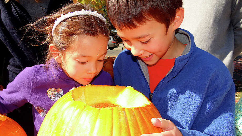 Abigail and Zachary Yan, 6 and 9, of Fairfield, peer inside a pumpkin at the annual pumpkin carving Sunday at St. Paul's Church. Photo: Mike Lauterborn / Fairfield Citizen contributed