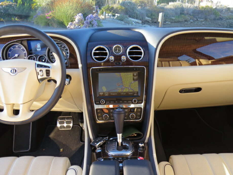"Being a Bentley, the Flying Spur  has to have a cross-cultural relationship with the past. Prominent on the dashboard are big, chromed blower vents that can be closed off with push-pull chrome knobs. It's practically pre-war. The wood (""dark fiddleback eucalyptus"")  is impeccably done and the controls are pretty straightforward. In a sop to the 21st century, there is a full-on navigation system and a rear-view camera."
